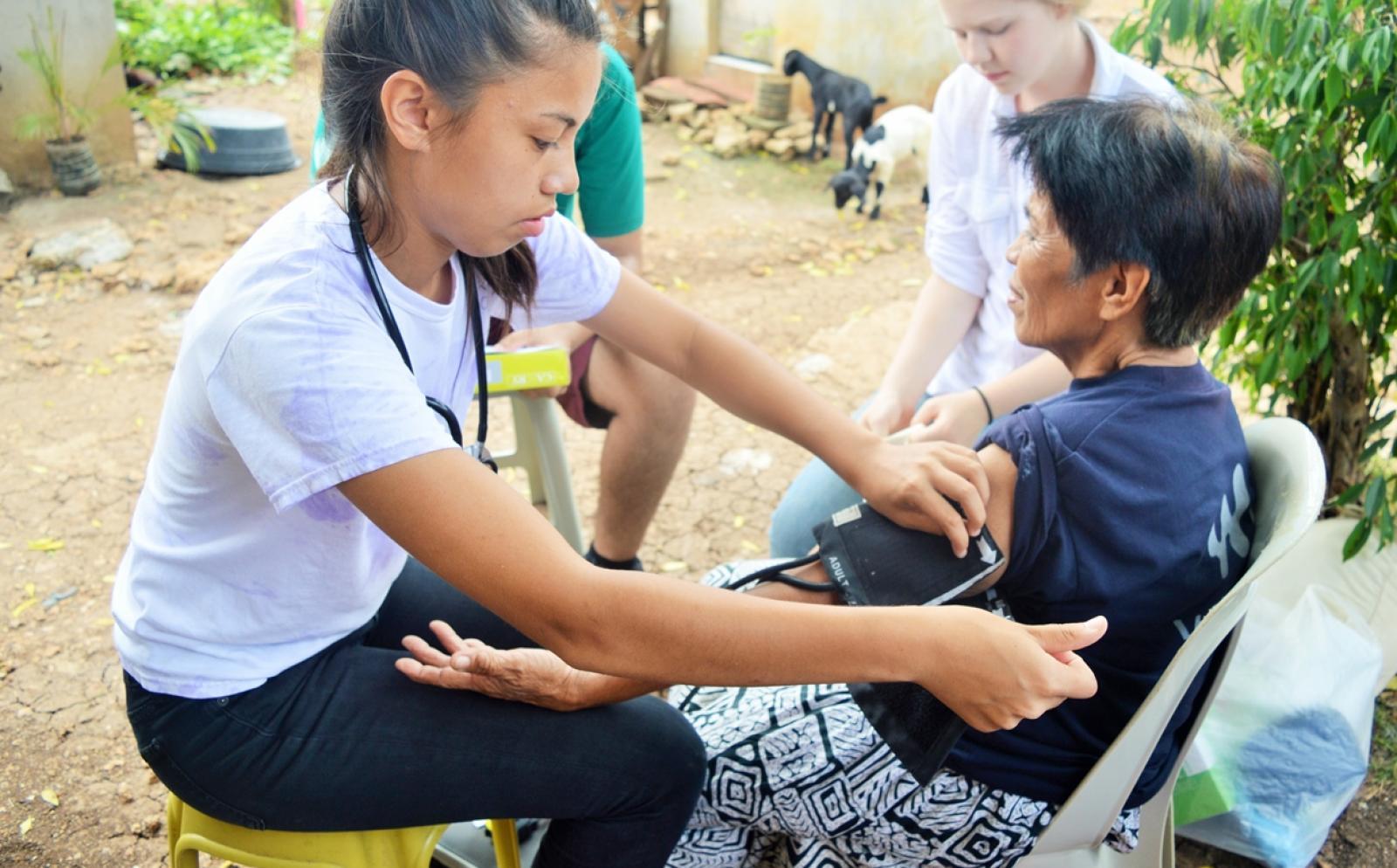 フィリピンの地域住民の血圧測定に取り組む高校生の公衆衛生ボランティア